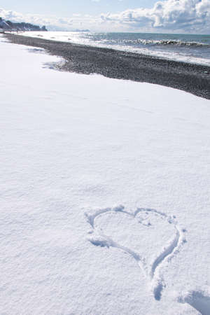 Heart shaped form on white snow with rocky beacj and sea view onthe background.Vertical blank space image. Banco de Imagens