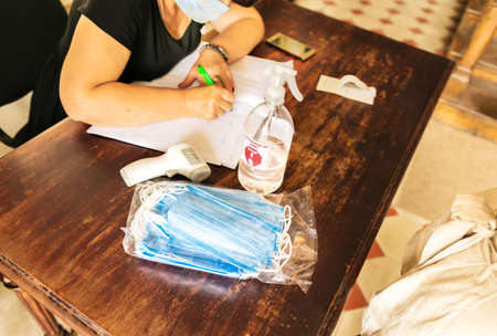 Check up table with bag of masks, termometer , disinfectant spray and woman filling  registration papers of visitors in a museum in Republic of Georgia. Pandemic safety requirememts 2020. Stockfoto