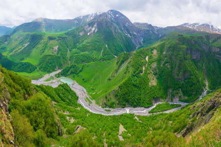 Aerial  panoramic view to scenic green  caucasus mountains with passing river at the bottom in Kazbegi national park.