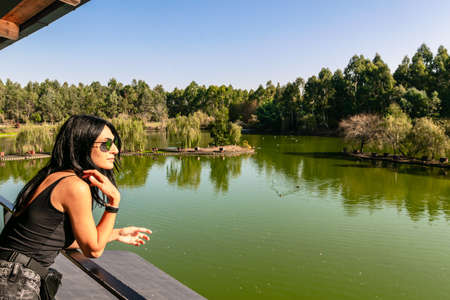 Caucasian woman on viewpoint platform looks right with green nature and lake in the background. Blank space image. Dendrological park.Georgia.