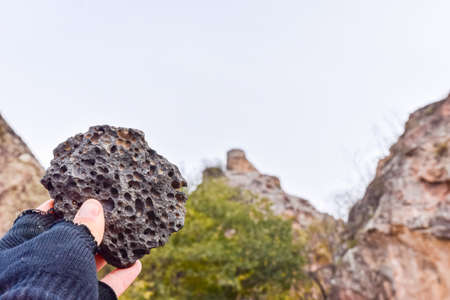 Unique peace of rock material in hand with blurred fortress structure in the background.