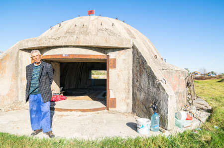 Old male albanian person stands by old italian bunker converted to home. Albania Unusual homes and living conditions.27 sep. 2018. Appolonia. Macedonia