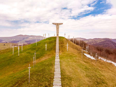 Drone view female tourist walk up stairs in Didgori - historical site memorial. Georgia heritage sightseeing landmarks
