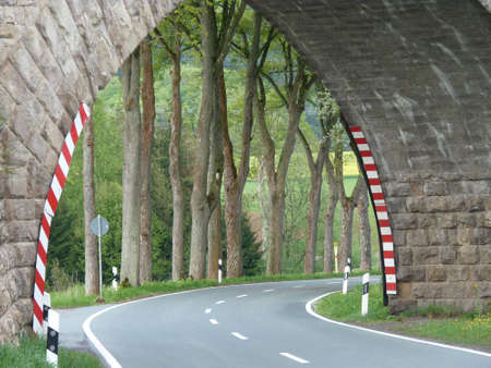 Arch bridge over an empty country road with a view of trees and fields Standard-Bild
