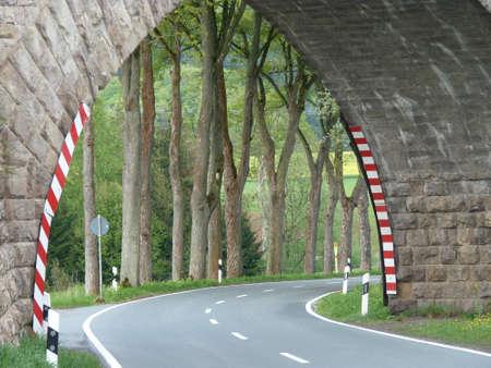 Bogenbrücke über eine leere Landstraße mit einem Blick auf die Bäume und Felder Lizenzfreie Bilder