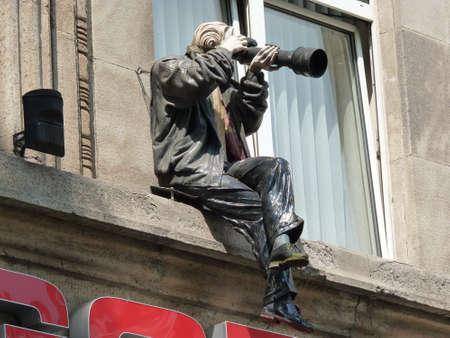 Köln, Deutschland - 15. Juli 2013 - Eine Puppe als Fotograf mit einer Kamera in der Hand sitzt auf dem Fensterbrett eines Geschäftshauses, Köln, Deutschland Editorial
