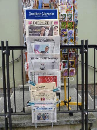 Zeitungen und Postkarten vor einem Geschäft