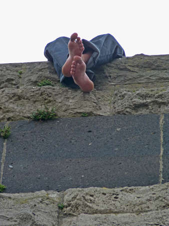 Young man with unshod feet sitting on a wall, Cologne Standard-Bild