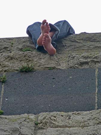 Junger Mann mit nackten Füßen sitzt auf einer Mauer, Köln