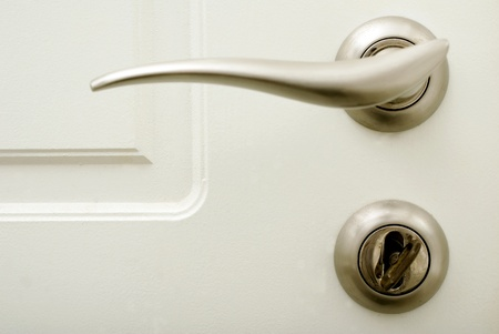 reverberation: white house door with stainless door handle and lock with key Stock Photo