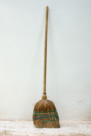 old classic wooden straw Broomstick against wall outdoor Stock Photo