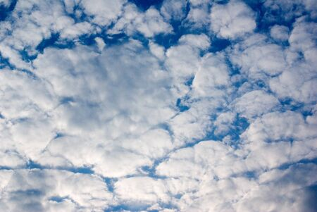 background of white fluffy clouds in a dark blue sky Stock Photo