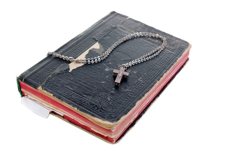 silver cross on old bible with leather cover isolated photo