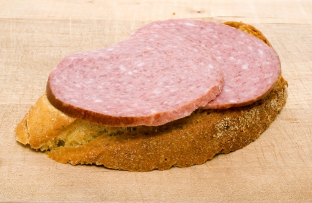 bread slice with salami on wooden kitchen cutting board