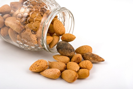 almonds in glass pot on white