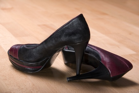 pair of duo color high heels side by side on light wooden floor