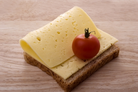 open sandiwich with cheese and cherry tomato on a wooden cutting board
