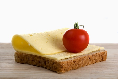 bread slice with cheese and a cherry tomato on a wooden kitchen chopping board Stock Photo
