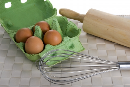 four eggs, ballon whisk and rolling pin on a bamboo place mat Stock Photo