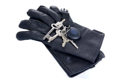 group of keys on black leather gloves isolated on white