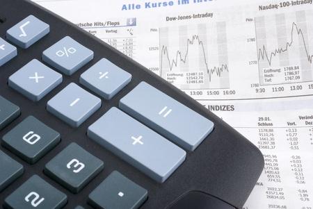 dow: calculator on a financial newspaper showing dow jones and nasdaq graphs