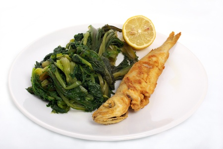 fried fish with lemonand vegetables in white dish Stock Photo
