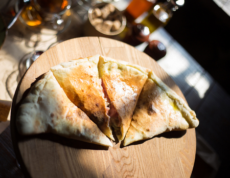 Closed pizza calzone is cut into pieces on a wooden plate Stock Photo
