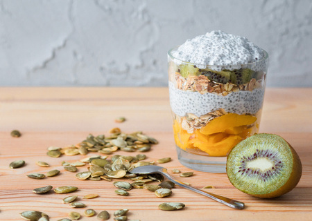 Healthy vanilla pudding of a chia in a glass with granola, mango and a kiwi. On a wooden table. Front view
