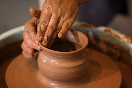 Roterende pottenbakkersschijf en aardewerk erop van bovenaf genomen. A beeldhouwt zijn handen met een beker van klei op een pottenbakkersschijf. Handen in klei. Proces van. Zijaanzicht Stockfoto