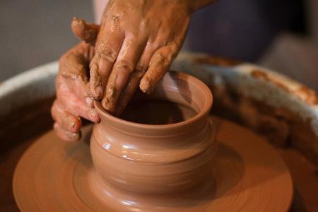 Ruota del vasaio rotante e articoli di argilla su di esso presi dall'alto. A scolpisce le sue mani con una tazza di argilla su un tornio da vasaio. Mani in argilla. Processo di. Vista laterale Archivio Fotografico