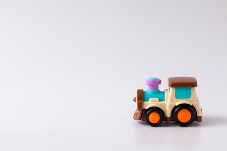 Colorful plastic train toy on white background. Side view