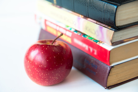 Red mature juicy apple near books. On a white table. Front view