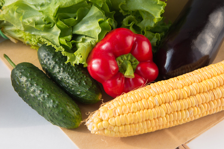 Paper bag full of fresh vegetables on light background. Grocery shopping bag. Sweet pepper, cucumbers, corn, salad, eggplant. Side view Reklamní fotografie