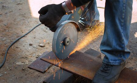 Hands cut metal plate with steel cutter tool. The Electrical saw produces a hot spark. Construction concept
