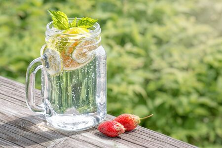 Lemonade with a lime and mint in a glass jar. Green grass in the background. Summer beverage Archivio Fotografico