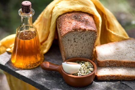 Home-made fresh bread, bottle with sunflower oil, pumpkin sunflower seeds and eggs, on an old wooden board in a summer garden. 版權商用圖片