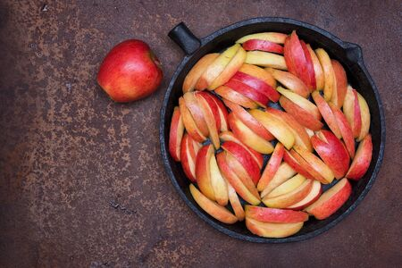 The apples cut by pieces and whole red apple in a pig-iron form for roasting  on a rusty metal surface. Side view.