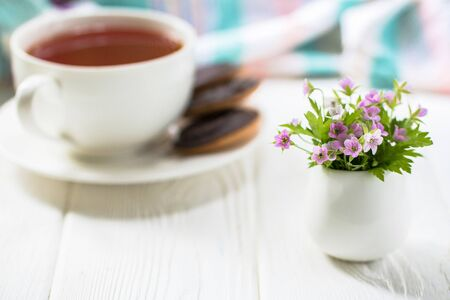 Miniature Purple flowers in a white vase on a white table with a mug of tea and cookies in the background. Front view
