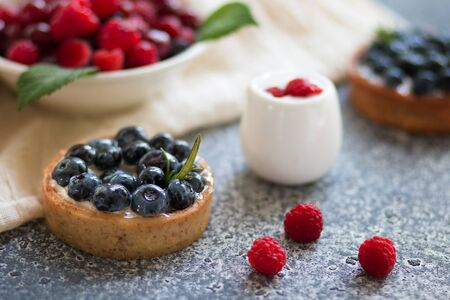 Tartalets with blueberry berries, plate with fresh raspberry and dairy with sour cream on the grey surface. Selective focus. Front View