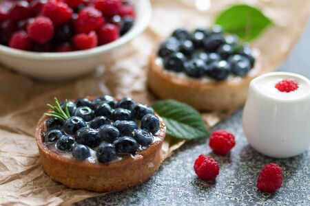 tartaletas with blueberry berries, plate with fresh raspberry and dairy with sour cream on the grey surface. Selective focus. Front View Stock fotó