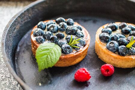 Delicious blueberry tartalets with vanilla cream and fresh raspberry berries on a black cast iron plate. Close up. Top view.