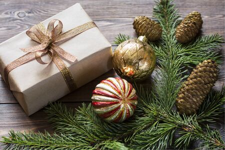 Christmas composition of gold Christmas balls, gift, spruce branches on a wooden brown surface.