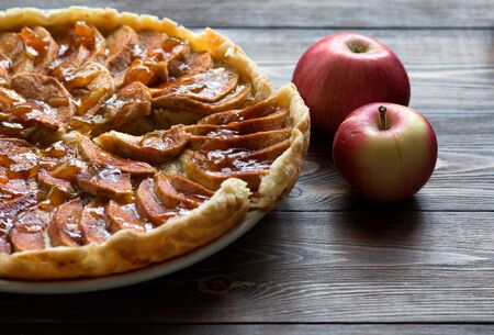 Apple pie with fresh apple and caramel sauce on a plate on a dark wooden surface. Front view. Baking concept in autumn.