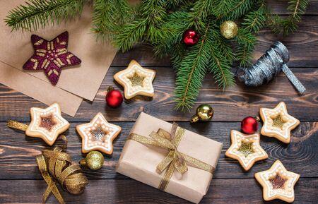 Weihnachtsgeschenk auf braunem Holztisch mit Fichtenzweigen, hausgemachten Keksen und Weihnachtsbaumspielzeug. Ansicht von oben. Neujahr und Weihnachten.