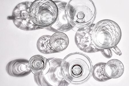 Different glasses, shot glasses and glass mugs on a white surface. Hard light and shadow. Top view. Flatlay