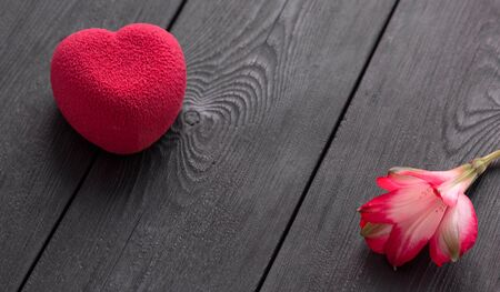 Valentines day concept. Red heart velvet cake on a wooden black background with a delicate Alstroemeria flower. Sweet present. A symbol of love happiness and devotion. Top view.  Copy space