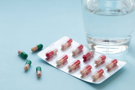 Capsules in blister with water in a clear glass cup on a grey surface. Medicine concept. Front view. Copy space