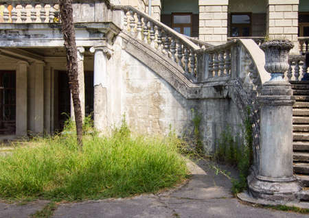 Ancient staircase with stone balusters on a background of green vegetation