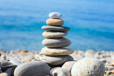 Pyramid of sea pebbles on the beach against the sea on a Sunny day Stock Photo
