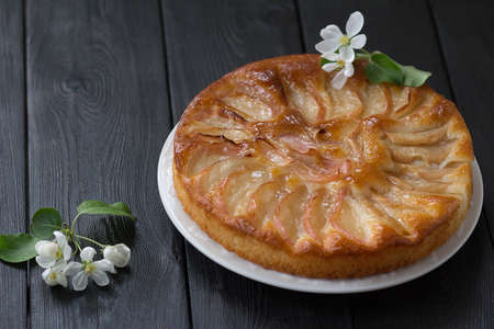 Freshly baked apple pie on a white plate with apple tree flowers on a black table.